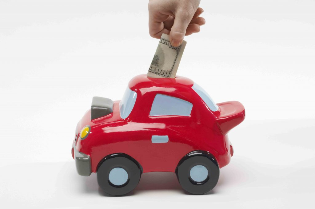 Putting money into car shaped piggy bank - delayed gratification to get what you really want