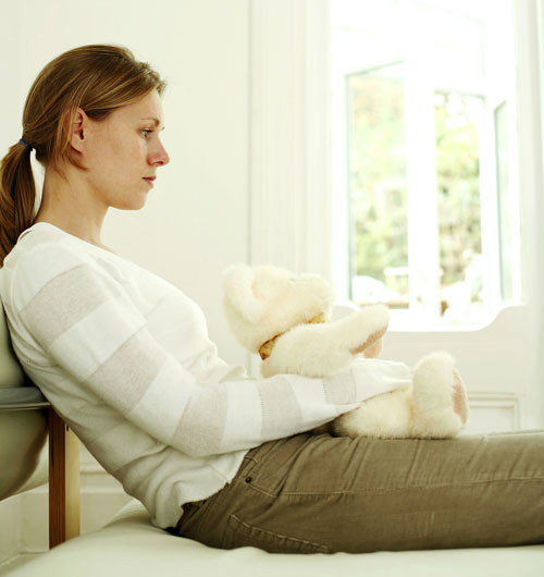 Sad and disappointed woman hugging teddy bear while daydreaming