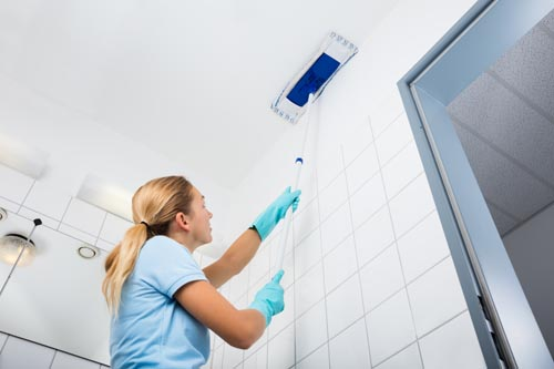 Woman using microfiber mop to clean ceiling