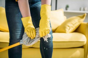 image of woman wearing yellow gloves wringing mop to clean floor