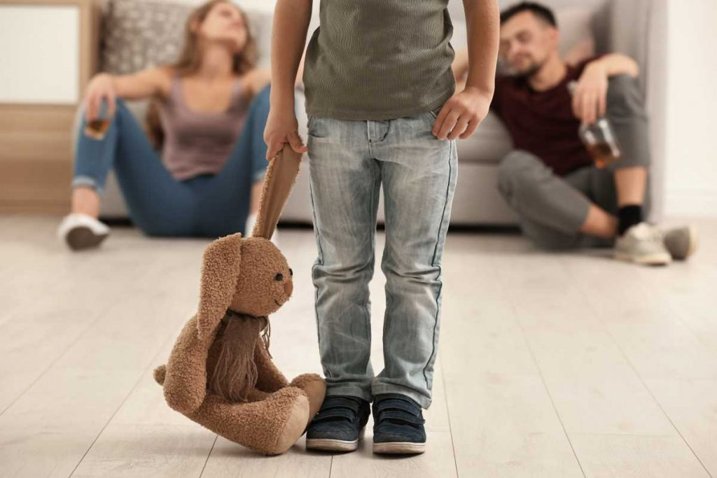 image of a child with their stuffed bunny while parents drink alcohol in the background