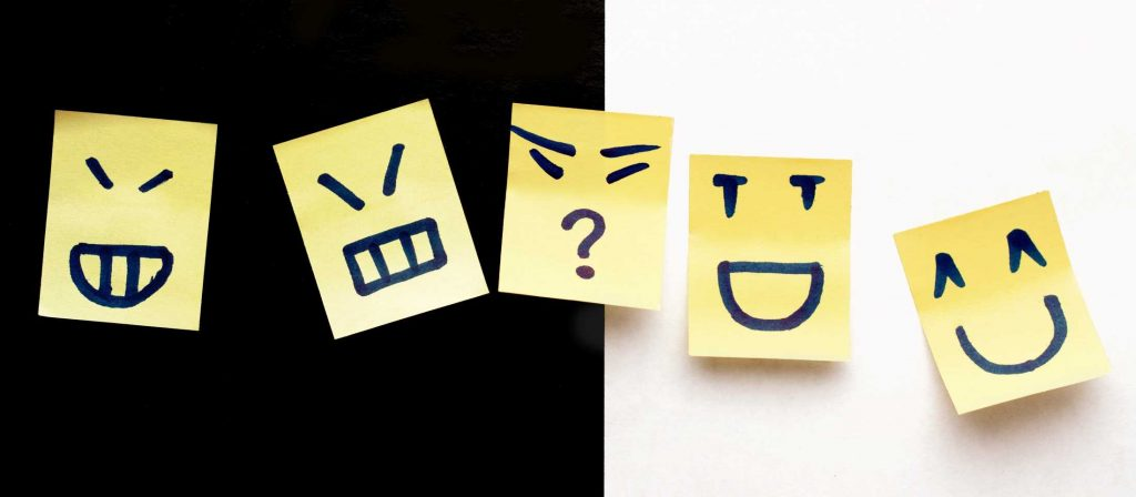 sticky notes depicting different moods - faking happy, neutral, unknown, laughing and smiling
