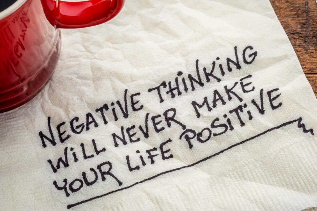 napkin under a red coffee cup that reads 'negative thinking will never make your life positive'