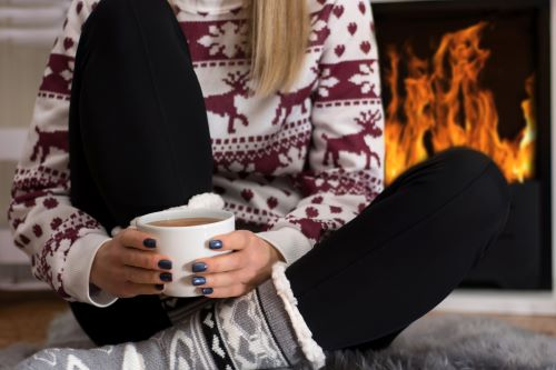 woman drinking coffee in front of fireplace during the holidays