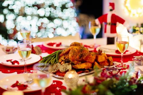 Image of perfectly decorated festive dinner table with glowing christmas tree lights in the background