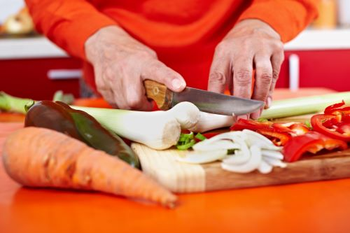 Senior woman hands chopping vegetables on a wooden board in the kitchen