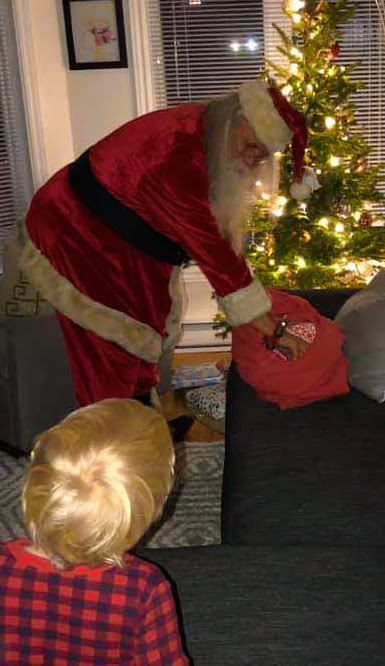 Santa placing little boys presents under tree