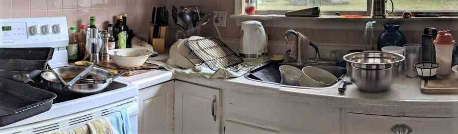 Image of kitchen counter covered in dirty dishes and kitchen sink full of dirty dishes and stove top covered in dirty pots and pans